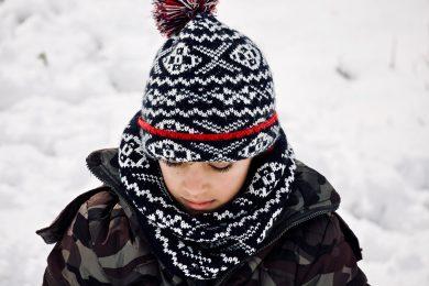 Enfant qui porte un bonnet et une écharpe assortis ainsi qu'une doudoune